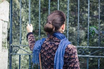 Young woman standing outside some gates
