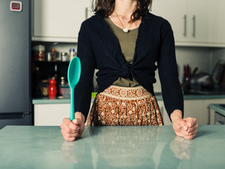 Confident woman with spoon in kitchen