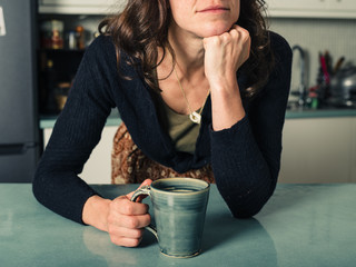 Young woman daydreaming with coffee in kitchen