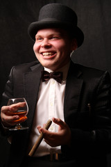 the young man in a black tuxedo and a hat takes a cigar