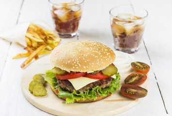 Big burger, french fries, lemonade on a white wooden background
