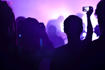 A fan shoots video of a rock concert to a mobile phone, Metall live concert, blurry background