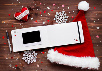 Christmas and New Year background with old fashioned camera, red Santa's hat, photo frame and notepad.