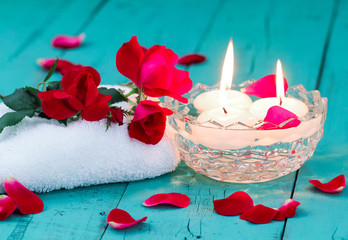 Spa composition of red roses and aroma candles on teal blue background