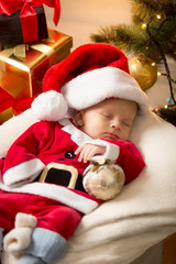 cute baby boy in Santa costume sleeping ext to Christmas gifts