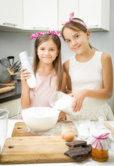 two sister mixing ingredients for dough in big bowl on kitchen