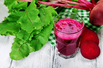 Glass of beet juice with vegetables on table close up