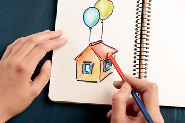Female hands drawing colorful house in notebook on wooden table, closeup