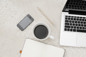 Laptop smart phone cup of coffee and notebook located on carpet