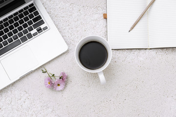 Laptop, cup of coffee and notebook located on carpet background