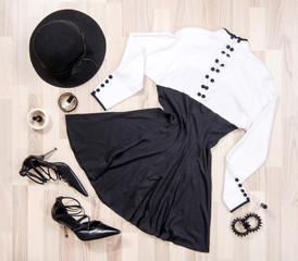 Cute dress with buttons and accessories arranged on the floor. Woman black and white dress with accessories, high heels, hat, bracelets lied down.