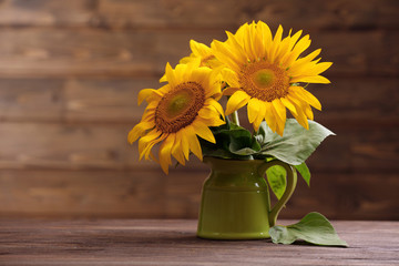 Beautiful bright sunflowers in pitcher on wooden background