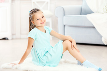 Little cute girl sitting on carpet, on home interior background