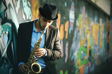 Young man with saxophone outside near the old painted wall