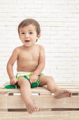 adorable toddler sitting on wooden box