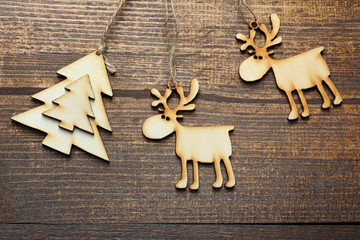 wooden tree decorations in the shape of a deer and trees on a brown wooden background
