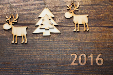 wooden tree decorations in the shape of a deer and trees on a brown wooden background with inscription