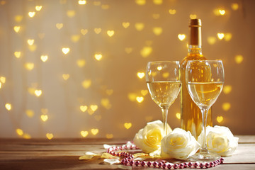 Glasses of wine, white roses and a bottle, on blurred background