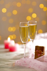 Glasses of wine, a gift in the box and candles, on blurred background