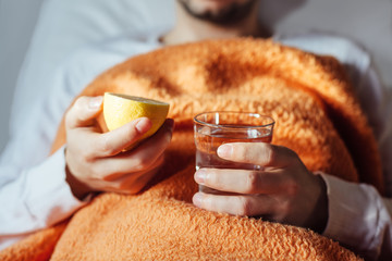 Sick man in bed with fresh glass of water and lemon