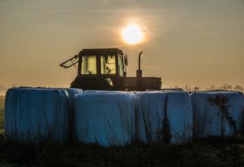 Strohballen mit Traktor in der Morgendämmerung