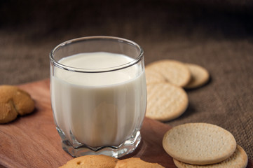 A glass of milk with cookies on a wooden board on a background sacking, burlap,