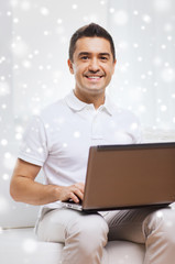 happy man working with laptop computer at home