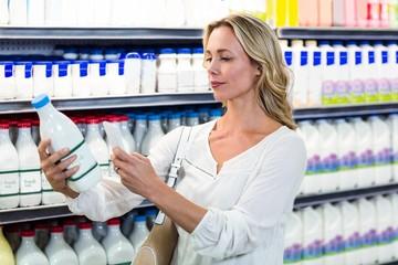 Beautiful woman taking a picture of milk bottle