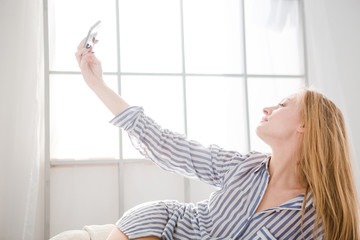 Lovely woman lying and taking photo of herself using cellphone