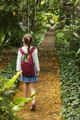 Little girl is walking on the botanic park.