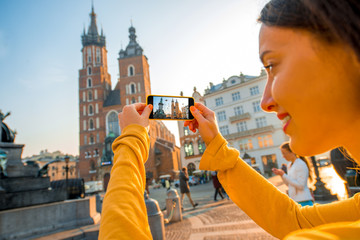 Autocollant pour porte Cracovie Female traveler photographing with mobile phone in Krakow