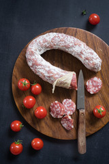 Overhead view of french salami and cherry tomatoes on cutting board