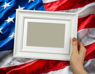 Wooden frame in woman hands on the background of flapping flag USA with wave