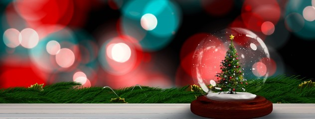 Composite image of christmas tree in snow globe