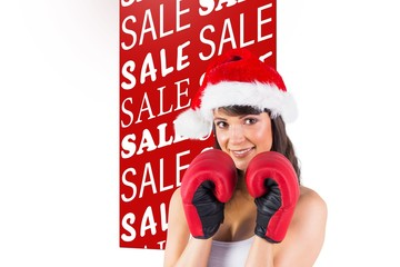 Composite image of festive brunette with boxing gloves
