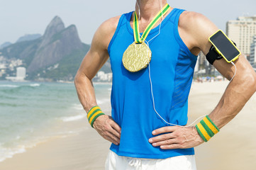 Gold medal athlete wearing mobile phone technology armband stands listening to motivational music outdoors on Ipanema Beach Rio de Janeiro Brazil