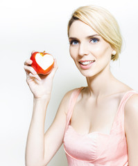 Beautiful woman with apple and love heart bite