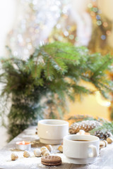 Coffee, tangerines, cookies and nuts in Christmas decor with Christmas tree, nuts and apples on colorful background bokeh