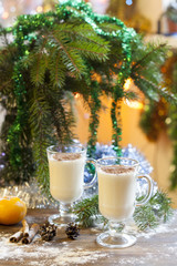 Vanilla panna cotta with chocolate,  tangerines, cones, cinnamon and nuts in Christmas decor with Christmas tree on colorful background bokeh