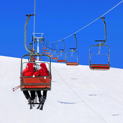Skiers couple in Christmas hats on ski lift against mountains