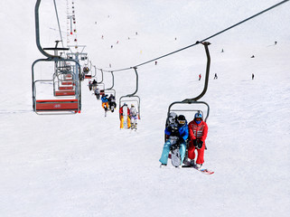 Skiers and snowboarders on ski lift against winter mountain land