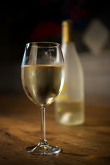 Glass of cold white wine with bottle on wooden table
