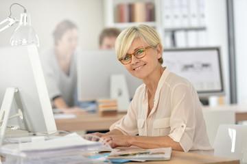 Smiling senior businesswoman working in office