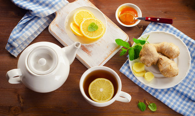 Tea with lemon, ginger, honey  and mint on a wooden background. View from above
