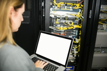 Technician using laptop to analyse server