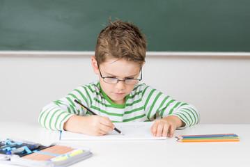 Kleines Kind mit Brille malt aufmerksam an einem Bild