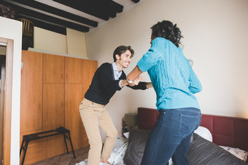 Young handsome mixed race couple in their house playing jumping