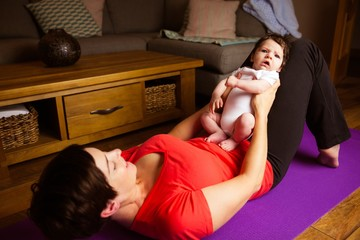 Smiling mother exercising with her baby