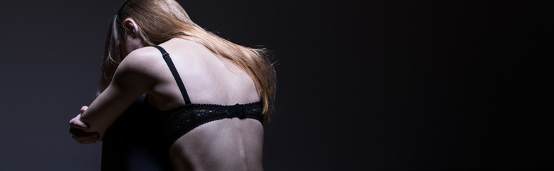 Anorexic girl on black background