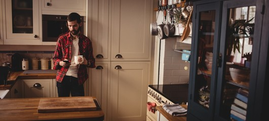 Handsome hipster relaxing in kitchen